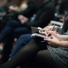 Blick auf eine Frau, die in einer Vorlesung Notizen macht